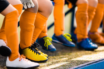 Footballers in soccer cleats. Youth athletes in soccer clothes. Young football players wearing...