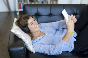 Young pretty long hair woman lying on a sofa making selfie on her phone