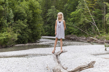 Girl standing on dead wood at the riverside