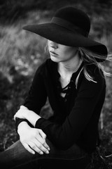 Young woman wearing black hat sitting on a meadow