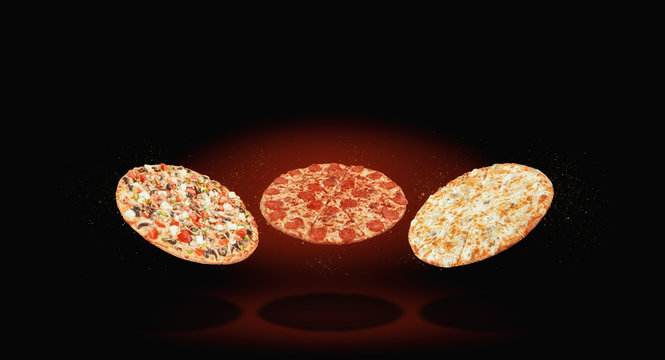 Three different pizza fly in the air against a dark background. menu and selection concept