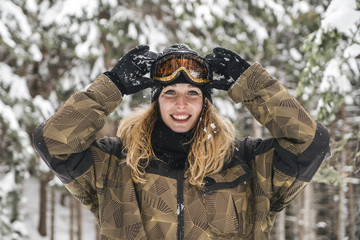 Portrait of happy young woman in skiwear in winter forest