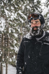 Smiling young man in skiwear in winter forest looking sideways