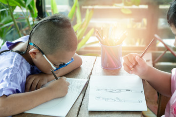 Boy and friends intend drawing a picture fun, enjoy drawing or write in book at home.