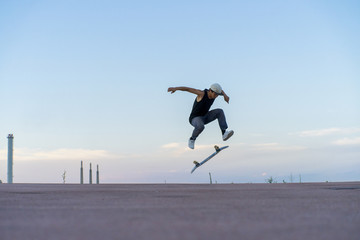 Young man doing a skateboard trick on a lane at dusk