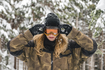 Young woman putting on ski goggles in winter forest