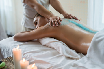 Young beautiful Asian woman relaxing in the spa massage and having salt scrub massage at back. healthy lifestyle and relaxation concept. Select focus hand of masseuse.