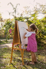 A pre-school girl painting at an easel in a garden.