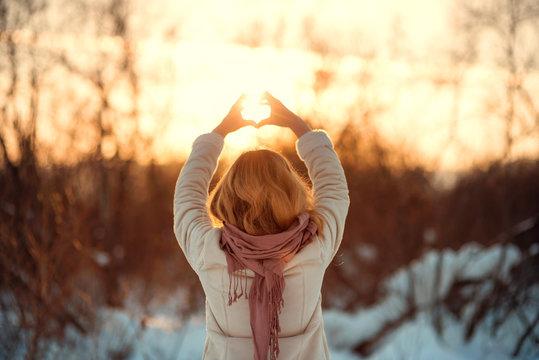 Девушка ловит солнце руками зимой на закате