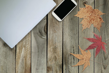 Top View of Work Space on Wooden Table with Laptop, Mobile Phone and Autumn Leaves