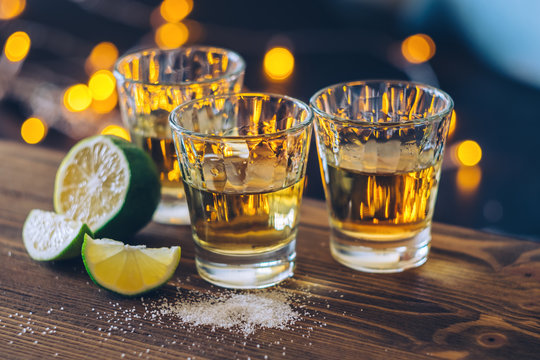 Shot of tequila with lime and salt on bokeh background