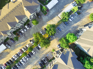 Aerial view of apartment garage with full of covered parking, cars and green trees of multi-floor residential buildings in Houston, Texas, US at sunset. Urban infrastructure and transportation concept