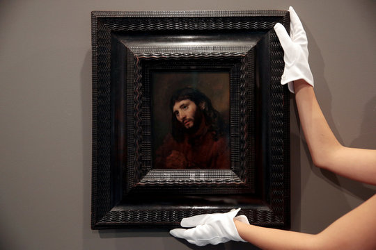 A member of Sotheby's staff adjusts the painting 'Study of the Head of a Young Man', by Dutch painter Rembrandt van Rijn on display at Sotheby's in Dubai
