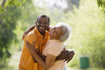 Portrait happy senior couple hugging outdoors in summer park together and smiling at camera