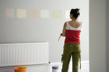 DIY woman choosing paint color swatches on room wall deciding on decor for home improvement