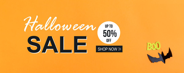 Halloween Sale message with paper bat overhead view on a solid color