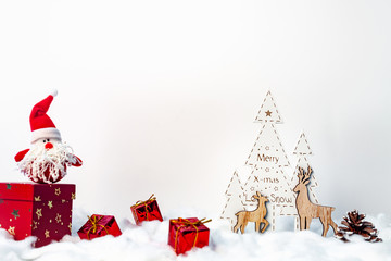 Christmas card with wooden Christmas trees, reindeers, red presents and plush Santa with white copy space background
