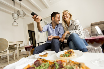 Young couple enjoying eating pizza and watching tv