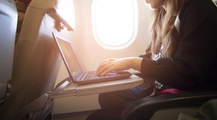 Woman is working with laptop while traveling on the plane at window seat.
