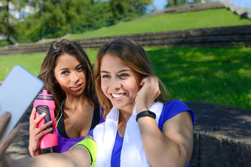 Millennial generation lifestyle concept - two sports girls taking a selfie and smiling after outdoors training on a sunny day.