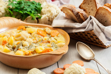 Vegetable soup with ingredients carrot, cauliflower, potato and parsley
