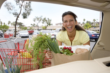 Smiling woman loads car with shopping bags from supermarket trolley at camera