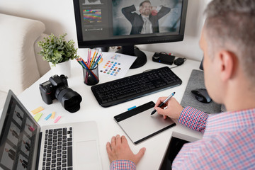 Graphic designer uses a pen and graphic tablet