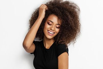 Wall Mural - Beautiful smiling african american woman touching her afro hairstyle isolated on white background