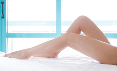 Slim beautiful female legs on bed. Cropped image of erotically lying on bed beautiful woman in bedroom. Crumpled white bedclothes.