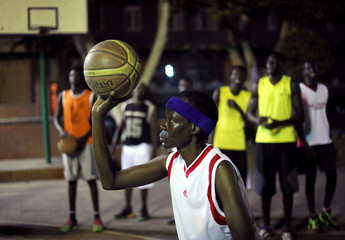 A Sudanese refugee holds up a ball during a basketball game in Cairo