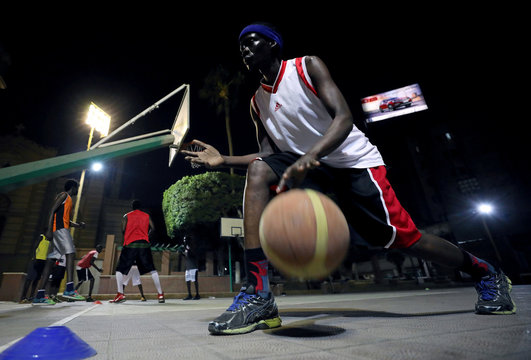 A Sudanese refugee dribbles the ball during a basketball game in Cairo