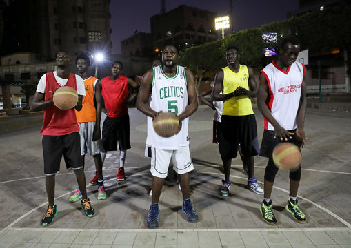 Sudanese refugees about to throw balls into a hoop during a basketball game in Cairo