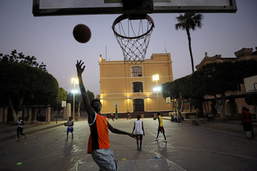 A Sudanese refugee jumps to the hoop during a basketball game in Cairo