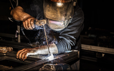 Professional welder in mask welds steel with electric torch tool