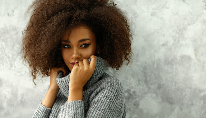 Wall Mural - Portrait of young black woman with an afro hair wear high-neck wool and cashmere sweater