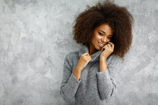 Portrait of young african american woman with an afro hair wear high-neck wool and cashmere sweater