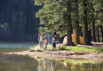 Family on camping trip in forest catching fish in lake