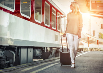Blonde woman with her luggage go near the red train on the person