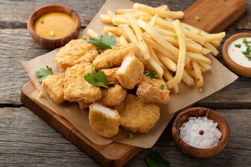 Chicken nuggets and french fries with various sauces on a wooden background. Top view Wall mural