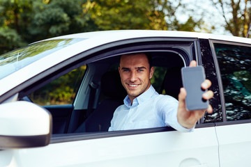 Smiling man sitting in his car and holding a cell phone