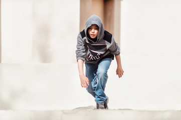 Portrait teenage boy on a street in a big city next to a high-rise building alone.