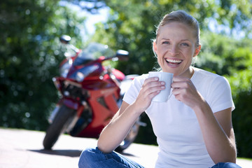 Portrait of smiling woman with coffee by motorbike