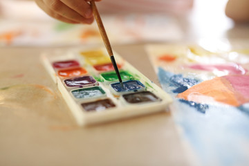 brushes and watercolor paints closeup.