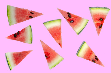 Watermelon slices cut into triangles. Pink background.