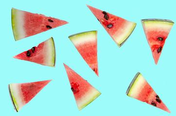 Watermelon slices cut into triangles bones. Blue background.