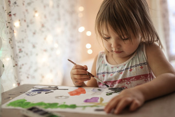 Toddler draw with brush and paint on paper in real