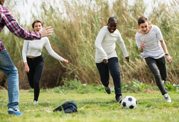 teenage friends playing football