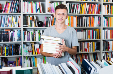Teenager holding pile of books