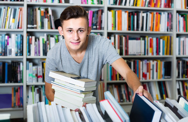 portrait of  boy standing among bookshelves and searching for book in library