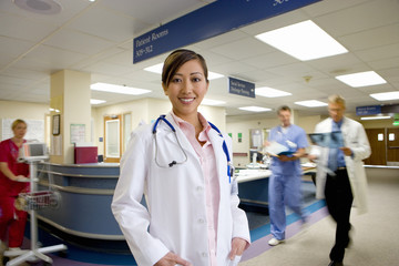 Portrait of young female doctor standing in busy hospital ward